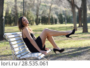 Купить «Portrait of funny woman, model of fashion with very long legs, sitting on a bench in an urban park, wearing black dress and high heels», фото № 28535061, снято 28 января 2015 г. (c) Ingram Publishing / Фотобанк Лори