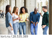 Купить «Multi-ethnic group of young people having fun together outdoors in urban background. group of beautiful women and men laughing together», фото № 28535389, снято 23 апреля 2017 г. (c) Ingram Publishing / Фотобанк Лори