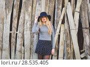 Купить «Beautiful young blonde woman, model of fashion, in rural background. Girl wearing sweater, skirt and hat.», фото № 28535405, снято 17 ноября 2015 г. (c) Ingram Publishing / Фотобанк Лори