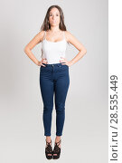 Купить «Portrait of young woman with long hair wearing white t-shirt and blue jeans on white background», фото № 28535449, снято 18 ноября 2014 г. (c) Ingram Publishing / Фотобанк Лори