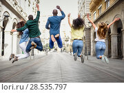 Купить «Multi-ethnic group of young people having fun together outdoors in urban background. group of people jumping together. Rear view.», фото № 28535797, снято 23 апреля 2017 г. (c) Ingram Publishing / Фотобанк Лори