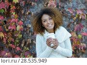 Купить «Beautiful young African American woman with afro hairstyle and green eyes wearing white winter dress. Girl drinking coffee in park sitting on grass wearing casual clothes smiling.», фото № 28535949, снято 25 ноября 2015 г. (c) Ingram Publishing / Фотобанк Лори