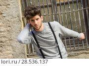 Купить «Portrait of young man wearing suspenders in urban background», фото № 28536137, снято 8 апреля 2014 г. (c) Ingram Publishing / Фотобанк Лори