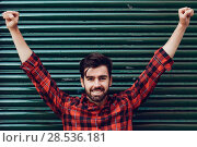 Купить «Young smiling man, open arms, wearing a plaid shirt with a green blind behind him. », фото № 28536181, снято 7 ноября 2017 г. (c) Ingram Publishing / Фотобанк Лори
