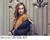 Купить «Blonde woman in urban background. Beautiful young girl wearing black leather jacket and mini skirt standing in the street. Pretty russian female with long wavy hair hairstyle and blue eyes.», фото № 28536321, снято 24 января 2017 г. (c) Ingram Publishing / Фотобанк Лори