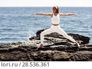Купить «Young woman doing yoga in the beach. Female wearing white sport clothes in warrior 2 figure with defocused sea background.», фото № 28536361, снято 29 марта 2017 г. (c) Ingram Publishing / Фотобанк Лори