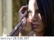 Купить «Make-up artist applying bright base color eyeshadow on model's eye and holding a shell with eyeshadow on background, close up», фото № 28536397, снято 23 декабря 2013 г. (c) Ingram Publishing / Фотобанк Лори