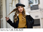 Купить «Blonde russian woman in urban background. Beautiful young girl wearing beret, black leather jacket and mini skirt standing in the street. Pretty female with long wavy hair hairstyle and blue eyes.», фото № 28536829, снято 24 января 2017 г. (c) Ingram Publishing / Фотобанк Лори