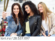 Купить «Group of multi-ethnic young women taking a selfie photograph together outdoors. Blonde, brunette and mixed females wearing casual clothes in urban background.», фото № 28537097, снято 23 апреля 2017 г. (c) Ingram Publishing / Фотобанк Лори