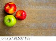 Купить «Три яблока на деревянном фоне. Одно зеленое и два красных.», фото № 28537185, снято 22 октября 2017 г. (c) Сергей Васильев / Фотобанк Лори