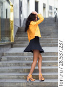 Купить «Young brunette woman, model of fashion, wearing orange modern jacket and blue skirt dancing in stairs. Pretty caucasian girl with long wavy hairstyle. Funny female in urban background.», фото № 28537237, снято 11 марта 2017 г. (c) Ingram Publishing / Фотобанк Лори