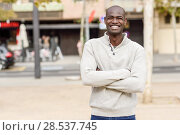 Купить «Black young man with arms crossed smiling in urban background. Young african guy with shaved head wearing casual clothes.», фото № 28537745, снято 20 ноября 2016 г. (c) Ingram Publishing / Фотобанк Лори