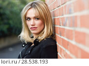 Купить «Pretty blonde woman in urban background. Young girl wearing black zipper jacket standing in the street. Pretty female with straight hair hairstyle and blue eyes on brick wall.», фото № 28538193, снято 22 января 2017 г. (c) Ingram Publishing / Фотобанк Лори
