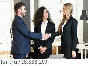 Купить «Multi-ethnic group of three businesspeople meeting in a modern office. Caucasian man and woman shaking hands wearing suit.», фото № 28538209, снято 23 апреля 2017 г. (c) Ingram Publishing / Фотобанк Лори