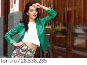 Купить «Young brunette woman, model of fashion, wearing green modern jacket and flower pants. Pretty caucasian girl with long wavy hairstyle. Female with red lips in urban background.», фото № 28538285, снято 11 марта 2017 г. (c) Ingram Publishing / Фотобанк Лори
