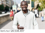 Купить «Black young man with a smartphone in his hand in urban background. Young african guy with shaved head wearing casual clothes and white headphones.», фото № 28538497, снято 20 ноября 2016 г. (c) Ingram Publishing / Фотобанк Лори