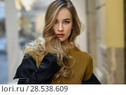 Blonde woman in urban background. Beautiful young girl wearing black leather jacket and mini skirt standing in the street. Pretty russian female with long wavy hair hairstyle and blue eyes. Стоковое фото, фотограф Javier Sánchez Mingorance / Ingram Publishing / Фотобанк Лори