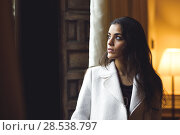 Купить «Beautiful young woman posing near a window in her bedroom. Brunette girl wearing white coat.», фото № 28538797, снято 10 февраля 2016 г. (c) Ingram Publishing / Фотобанк Лори
