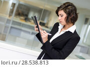 Купить «Portrait of a business woman in an office. Businesswoman writting with a folder in her hands in a modern office.», фото № 28538813, снято 14 января 2014 г. (c) Ingram Publishing / Фотобанк Лори
