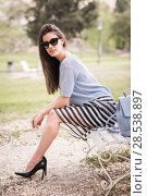 Купить «Young woman with beautiful legs in urban background wearing casual clothes. Girl with sunglasses wearing striped skirt and sweater sitting on a bench of an urban park», фото № 28538897, снято 14 апреля 2015 г. (c) Ingram Publishing / Фотобанк Лори