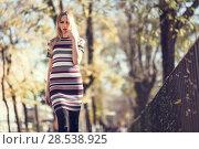 Купить «Young blonde woman walking in the street. Beautiful girl in urban background wearing striped dress and black tights. Female with straight hair.», фото № 28538925, снято 11 декабря 2016 г. (c) Ingram Publishing / Фотобанк Лори