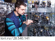 Купить «Male choosing baitcasting reel for rod for fishing in the sports shop», фото № 28540141, снято 16 января 2018 г. (c) Яков Филимонов / Фотобанк Лори