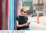 Купить «Woman using smartphones against colorful graffiti wall in New York city, USA.», фото № 28543621, снято 31 марта 2020 г. (c) Matej Kastelic / Фотобанк Лори