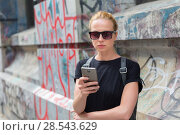 Купить «Woman using smartphones against colorful graffiti wall in New York city, USA.», фото № 28543629, снято 31 марта 2020 г. (c) Matej Kastelic / Фотобанк Лори