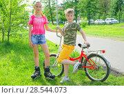 Купить «Подростки,брат и сестра после активных тренировок на роликовых коньках и езды на велосипеде в парке», фото № 28544073, снято 6 июня 2018 г. (c) Круглов Олег / Фотобанк Лори