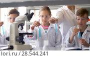 Купить «teacher and students studying chemistry at school», видеоролик № 28544241, снято 28 мая 2018 г. (c) Syda Productions / Фотобанк Лори