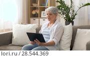 Купить «senior woman having video chat on tablet pc», видеоролик № 28544369, снято 30 мая 2018 г. (c) Syda Productions / Фотобанк Лори
