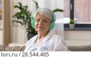 Купить «senior woman in headphones listening to music», видеоролик № 28544485, снято 29 мая 2018 г. (c) Syda Productions / Фотобанк Лори