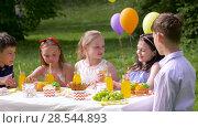 Купить «happy kids on birthday party at summer garden», видеоролик № 28544893, снято 5 июня 2018 г. (c) Syda Productions / Фотобанк Лори