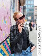 Купить «Woman talking on smartphone leaning against colorful graffiti wall in New York city, USA.», фото № 28546989, снято 4 апреля 2020 г. (c) Matej Kastelic / Фотобанк Лори