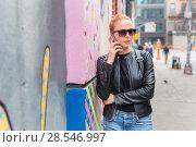 Купить «Woman talking on smartphone leaning against colorful graffiti wall in New York city, USA.», фото № 28546997, снято 4 апреля 2020 г. (c) Matej Kastelic / Фотобанк Лори