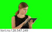 Young woman using a tablet on a Green Screen. Стоковое видео, видеограф Vasily Alexandrovich Gronskiy / Фотобанк Лори