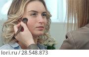 Купить «Backstage in the film. Make-up artist doing professional make-up for actress», фото № 28548873, снято 17 ноября 2018 г. (c) Vasily Alexandrovich Gronskiy / Фотобанк Лори