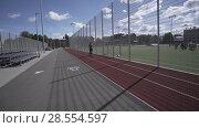 Купить «Electric Longboard summer ride on red sport stadium with playground», видеоролик № 28554597, снято 9 июня 2018 г. (c) Aleksejs Bergmanis / Фотобанк Лори