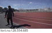 Купить «Electric Longboard man in sweatshirt and hat ride on red sport stadium with playground», видеоролик № 28554685, снято 9 июня 2018 г. (c) Aleksejs Bergmanis / Фотобанк Лори