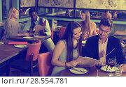 Купить «Happy couple discussing restaurant menu», фото № 28554781, снято 7 марта 2018 г. (c) Яков Филимонов / Фотобанк Лори