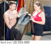 Купить «Young couple planning to surf, choosing boards and surfing suits in beach club», фото № 28555089, снято 30 апреля 2018 г. (c) Яков Филимонов / Фотобанк Лори