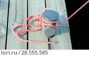 Купить «Закрепленный красный канат растягивается и стягивается на причале», видеоролик № 28555585, снято 10 июня 2018 г. (c) FMRU / Фотобанк Лори
