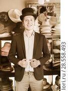 Купить «adult male shopping in botique and try on cylinder hat», фото № 28558493, снято 2 мая 2017 г. (c) Яков Филимонов / Фотобанк Лори
