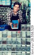 Купить «Man standing near the counter and selling details for plumbing in hardware shop», фото № 28558529, снято 4 мая 2017 г. (c) Яков Филимонов / Фотобанк Лори