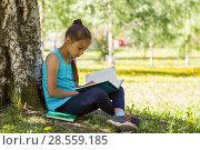 Купить «Девочка сидит на траве в парке с раскрытой книгой в руках и увлеченно читает», фото № 28559185, снято 29 мая 2018 г. (c) Лариса Капусткина / Фотобанк Лори