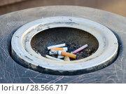 Купить «Окурки сигарет в пепельнице на городской улице», фото № 28566717, снято 12 мая 2018 г. (c) Ольга Коцюба / Фотобанк Лори