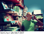 Купить «Happy man in front of difficult choice in store», фото № 28567597, снято 29 августа 2016 г. (c) Яков Филимонов / Фотобанк Лори