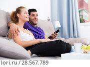 Купить «Cheerful couple on couch watching TV», фото № 28567789, снято 16 апреля 2019 г. (c) Яков Филимонов / Фотобанк Лори