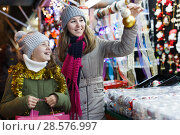 Купить «Smiling girl with woman are buying toys for X-mas tree», фото № 28576997, снято 19 декабря 2017 г. (c) Яков Филимонов / Фотобанк Лори