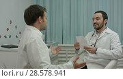 Купить «Happy young intern shows to mentor doctor results of their medical research work», видеоролик № 28578941, снято 24 ноября 2015 г. (c) Vasily Alexandrovich Gronskiy / Фотобанк Лори